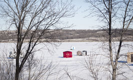 Fishing huts sitting on a snowy frozen lake in winter time. stock image