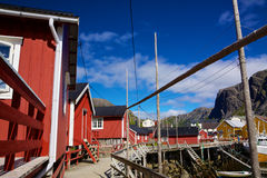 Fishing huts. Traditional old red fishing huts in picturesque village of Nusfjord on Lofoten islands, Norway, popular tourist destination Royalty Free Stock Images