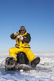 Fishing on Ice. Ice fisher man with beard fighting a fish Royalty Free Stock Images