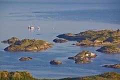 Fishing industry on tiny islands. Houses of fishermen on tiny islets on Lofoten Islands near Henningsvaer, Norway Royalty Free Stock Photo