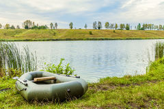 Fishing inflatable rubber boat standing on the shore of lake. Dinghy with oars Royalty Free Stock Image