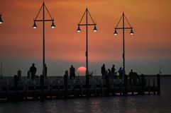 Family fishing on a jetty at sunset under lights Stock Photos