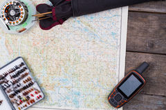 Fishing journey with fly-fishing tackles and map Royalty Free Stock Photo