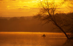 Fishing from a Kayak. An angler fishing from a kayak on a beautiful lake at sunrise royalty free stock image