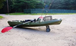 Fishing kayak on wheels paddle rods. Fishing kayak with rods and paddle ready for transportation to nearby river or lake , wheels from one of the site of boat stock photography