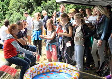 Fishing kids. Little girl playing on fishing and other kids and adulsts watching her during Children´s Day in Prague ZOO (31st May 2015, Czech Republic Royalty Free Stock Photo
