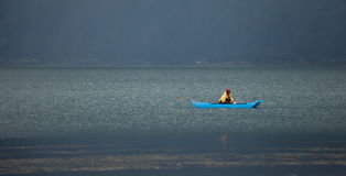 Fishing on Lake Batur. LAKE BATUR, BALI - JANUARY 21. Man fishing in boat on Lake Batur on January 21, 2012 in Bali, Indonesia. Fish is part of the stape diet on Royalty Free Stock Photography