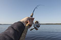 Fishing on a lake. clear blue sky. Fishing on a lake. Fishing rod with a reel in hand.clear  blue sky Royalty Free Stock Photography