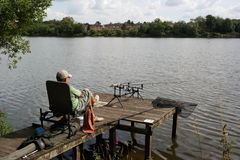 Fishing in lake. Man sat fishing on boardwalk of tree-lined lake sunlit net rods wearing cap Stock Images