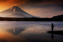 Fishing at lake with Mount Fujisan. Landscape of silhouette man fishing at Shoji lake with mount Fuji or Fujisan with water reflection and twilight sky during Stock Photography