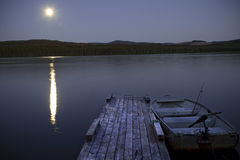Fishing Lake at Night with Moon. An awesome fishing lake is displayed with a bright moon reflecting off the water stock image