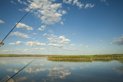 Fishing in a lake. Fishing rod and beautiful clouds reflrction in a lake Royalty Free Stock Image