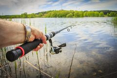Fishing on lake. Fishing rod in fisherman`s hand against lake in summer in nature on bright sunny day. To fish on river by spinning. fisherman is holding Royalty Free Stock Photos