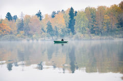 Fishing on the lake Senezh in Solnechnogorsk in the fall. The fog, the wind, the silhouette of a fisherman in a boat Royalty Free Stock Photography
