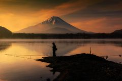 Fishing at Lake Shoji and Fujisan. Silhouette fishing leisure at Lake Shoji against Mountain fuji or mount Fujisan at sunrise with twilight sky in Yamanashi stock photos