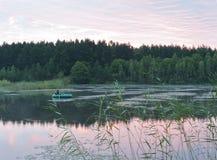 Fishing on the lake at sunrise Stock Photo