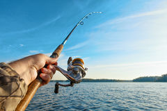 Fishing on a lake at sunrise. Fishing rod with a reel in hand Stock Photos