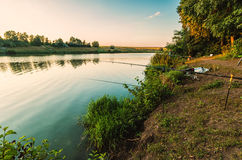 Fishing on the lake at sunrise. Fishing on the lake in the woods with rods Stock Image