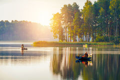 Fishing in a lake at sunshine. Fishing in a lake on a boat at sunshine with dog friend Royalty Free Stock Image