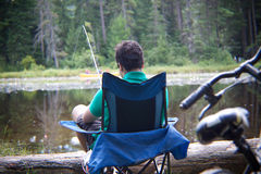 Fishing by the lake. A teenage boy fishing by the lakeside in his camp chair Stock Image