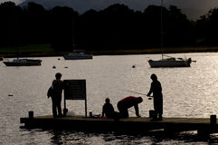 Fishing on Lake Windermere. Children fish from a pier on Lake Windemere, Lake District Royalty Free Stock Image