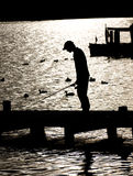 Fishing on Lake Windermere. Silhouette of boy fishing from a Jetty on Lake Windermere Stock Image
