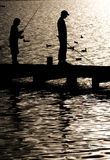 Fishing on Lake Windermere. Silhouette of boy fishing from a Jetty on Lake Windermere Royalty Free Stock Image