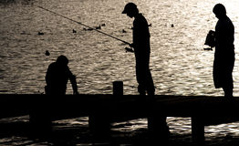 Fishing on Lake Windermere. Silhouette of boy fishing from a Jetty on Lake Windermere Stock Photo