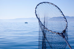 Fishing landing net in blue sea. At Mediterranean stock photography