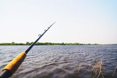 Fishing rod thrown in the waters of a river Royalty Free Stock Photography