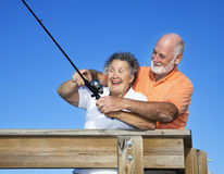 Fishing Lessons. Senior woman getting a fishing lesson from her husband Stock Photography
