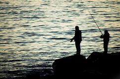 Fishing lessons from father to son Stock Images