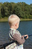 Fishing. The little boy. On the waterfront and a boat with a fishing rod Royalty Free Stock Photography