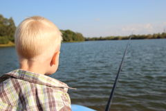 Fishing. The little boy. On the waterfront and a boat with a fishing rod Stock Images