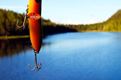 Fishing lure. Against a beautiful lake background Stock Image