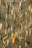 Fishing Lure Background. Vintage fishing lures hanging on a fish net Royalty Free Stock Images