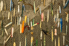 Fishing Lure Background. Vintage fishing lures hanging on a fish net Royalty Free Stock Image