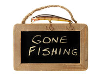 Fishing lure on top of gone fishing sign Stock Photography