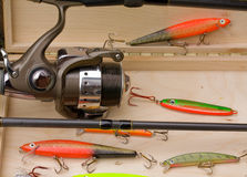 Fishing lures. Fishing rod and reel with fishing lures in a tackle box Stock Photography