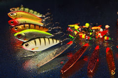 Fishing lures. Several ice fishing lures on blue water drop background Royalty Free Stock Images
