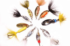 Fishing lures in a circle. Collection of Fishing lures particulalry spinners in a circle on a white background Stock Photography