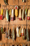Fishing lures hanging against wall. Set of fishing lures hanging against wooden wall Royalty Free Stock Image