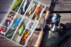 Fishing Lures in tackle boxes with spinning rod and net. On wooden pier stock images