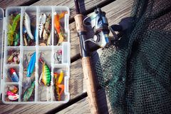 Fishing Lures in tackle boxes with spinning rod and net. On wooden pier stock image