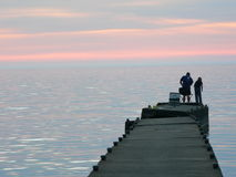 Fishing. Man and boy fishing from a concrete pier at dusk Royalty Free Stock Photo