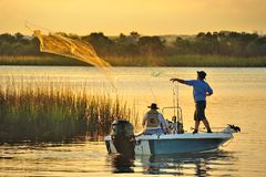 Fishing. Man throwing a net for bait fish Royalty Free Stock Photos