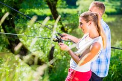 Fishing man and woman together with rod at the river side stock photo