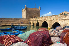 Fishing marina. Colored fishnets and boats with stone rampart and tower in old port in Essaouira, Morocco, Africa Royalty Free Stock Photo