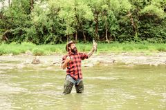 Fishing masculine hobby. Brutal man wear rubber boots stand in river water. Weekend activity. Fisher fishing equipment