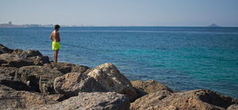 Fishing in the Mediterranean. A lone man, fishing off rocks, in the Mediterranean sea Royalty Free Stock Photos